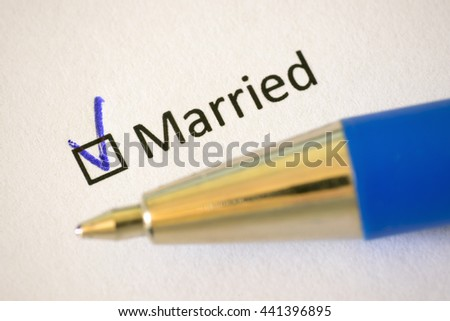 Questionnaire. Blue pen and the inscription MARRIED with check mark on the white paper