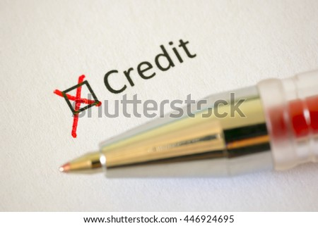 Questionnaire. Red pen and the inscription CREDIT with cross on the white paper - stock photo