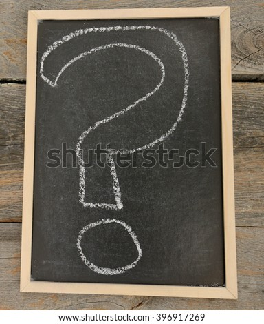 Questions mark written in chalk on a chalkboard on a rustic background - stock photo