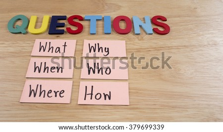 Questions what, when, where, why, who, how on wood background - stock photo
