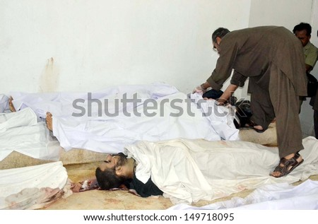 QUETTA, PAKISTAN - AUG 12: People gather near dead bodies of victims, who were killed in an exchange of fire with security forces during operation in the hilly areas on August 12, 2013 in Quetta.