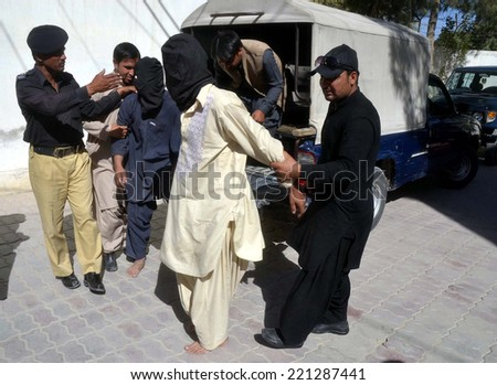 QUETTA, PAKISTAN - OCT 03: Police escorting criminals alleged in kidnapping of children  for ransom money in front of media during press conference on October 03, 2014 in Quetta.