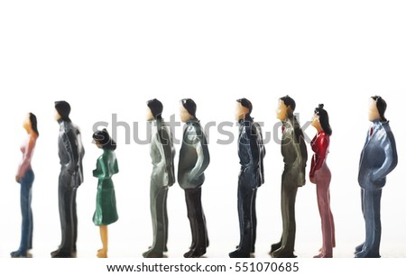 Queue of miniature model people in a line against white background