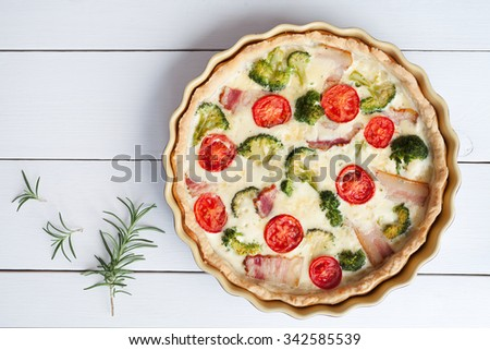 Quiche lorraine tart pie traditional homemade french food preparation recipe with cheese tomatoes broccoli and bacon in baking dish on white wooden table background. Rustic style - stock photo