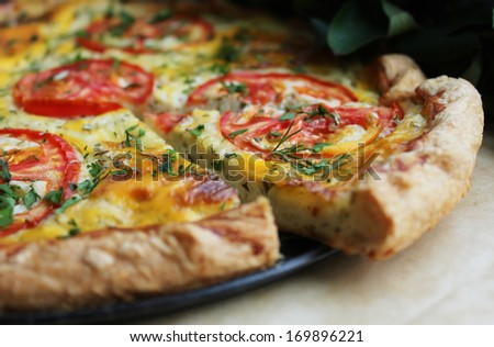 Quiche or pie with ripe tomatoes, cottage cheese filling, fresh herbs and assorted cheeses for a summer picnic - stock photo