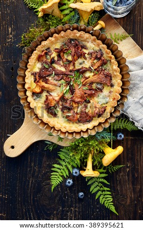 Quiche with chanterelle mushrooms and fresh savory on a wooden rustic table - stock photo