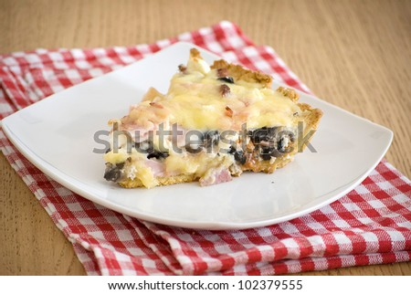 quiche with ham cheese salami muchrooms beans eggs in a white plate - stock photo