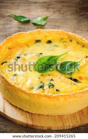 quiche with salmon and spinach on a dark wood background. toning. selective focus in front of the pie filling - stock photo