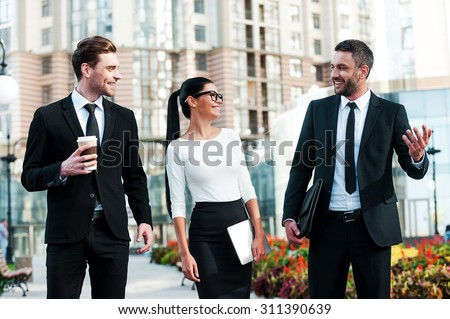 Quick briefing before meeting. Three cheerful young business people talking to each other while walking outdoors - stock photo