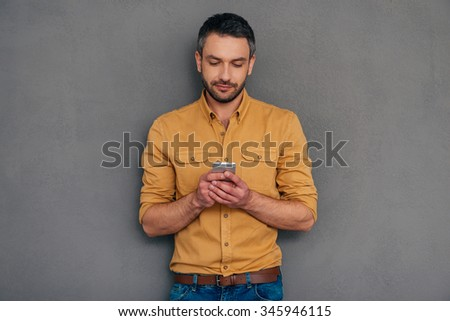 Quick message to friend. Confident mature man holding smart phone and looking at it while standing against grey background - stock photo