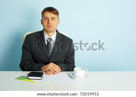 Quiet business young man sits at a desk in the office - stock photo