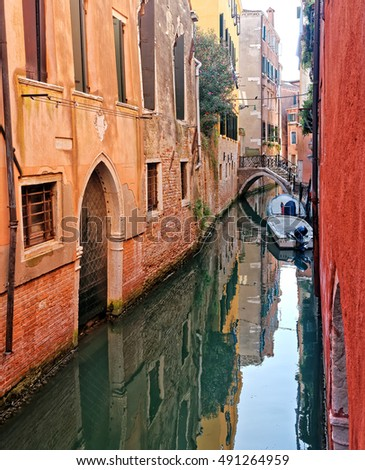 Quiet canal with boats and exquisite antique buildings in Venice, Italy