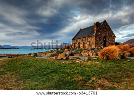 quiet church by a glacier lake against a mountain backdrop - stock photo
