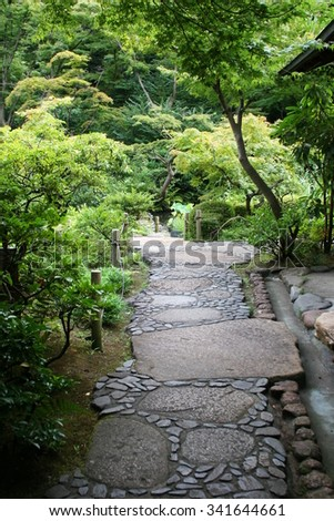 Quiet footpath in a Japanese garden with lots of greenery, peaceful and tranquil - stock photo