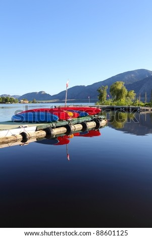 Quiet morning lake Osoyoos, BC, Canada. Colorful kayaks are laid out on a dock ready for use. - stock photo