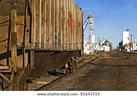 Quiet scene of a rural town with an old rusty rail-car covered with graffiti waiting on a rail siding. - stock photo