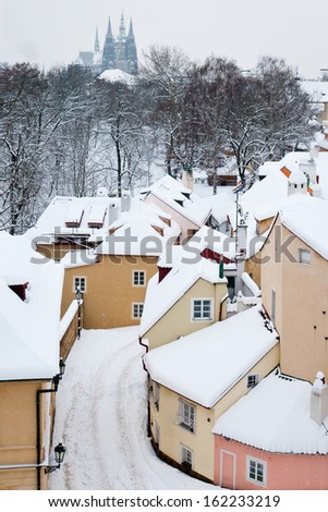 Quiet street with small houses in winter snow covered Prague - stock photo