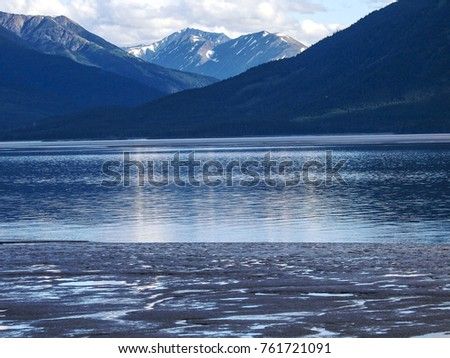 Quiet waters of Turnagain Arm surrounded by snowy mountains in Alaska, USA