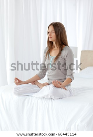 Quiet woman doing yoga exercises on the bed at home