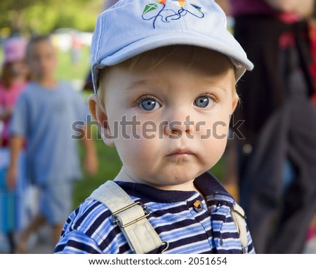 quiet young child with big blue eyes and a hat - stock photo