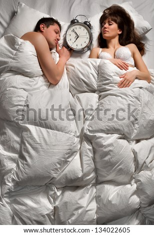 Quiet  young couple sleeping together and ignoring alarm clock bell - stock photo