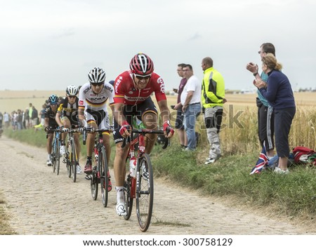 QUIEVY,FRANCE- JUL 07: Group of four cyclists riding on a cobblestone road during the stage 4 of Le Tour de France on 07 July,2015 in Quievy, France. - stock photo