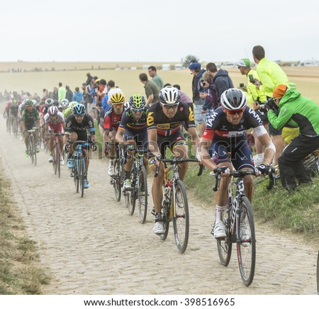 QUIEVY,FRANCE- JUL 07:The peloton riding on a cobblestone road  during the stage 4 of Le Tour de France in Quievy, France, on 07 July 2015