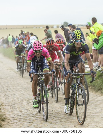 QUIEVY,FRANCE- JUL 07: The peloton riding on a cobblestoned road during the stage 4 of Le Tour de France on 07 July,2015 in Quievy, France. - stock photo
