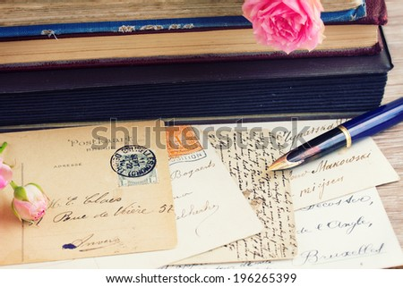 quill pen and antique letters on table with books - stock photo