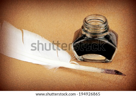 Quill pen and ink bottle on brown background. Vintage style image. - stock photo
