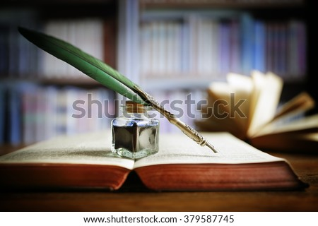 Quill pen and ink well resting on an old book in a library concept for literature, writing, author and history - stock photo