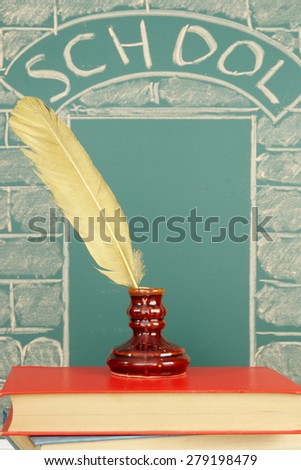 Quill pen in inkwell before entry school pictured with chalk on blackboard - stock photo