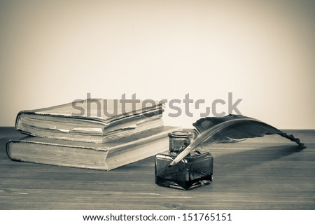 Quill pen, ink bottle, old books on table for vintage background - stock photo