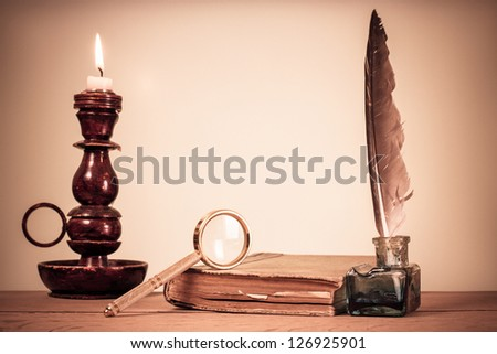 Quill pen, inkwell, book, magnifying glass and candle on the table - stock photo