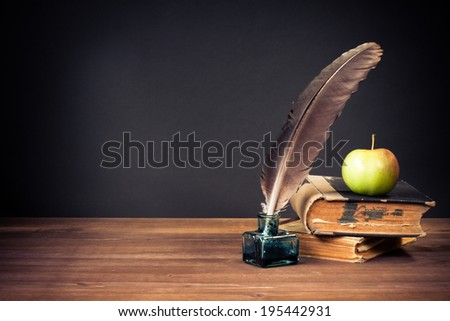 Quill pen, old books, apple on table for vintage background - stock photo