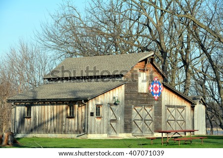 Quilt barn with picnic table and trees - stock photo