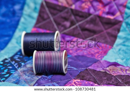 Quilt with quilting threads - stock photo