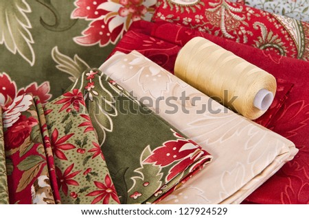 Quilting fabrics in different colors and patterns with quilting thread - stock photo