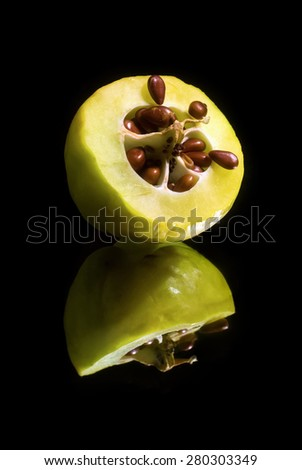 Quince cut in half with seeds on a black background with reflection. Vertical shot. - stock photo