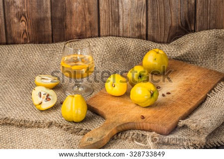 Quince fruits alcohol drink in a glass on a canvas background. - stock photo