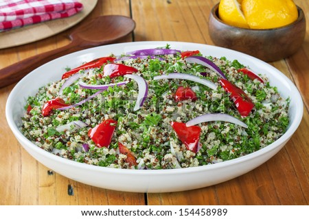 Quinoa and Amaranth salad, with parsley, red peppers, red onions, lemon juice and olive oil. Contains red, black and white quinoa. - stock photo