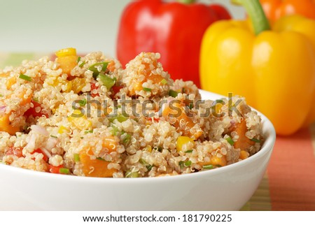 Quinoa, bell peppers, potato and other vegetables with red, orange and yellow bell peppers in the background - stock photo