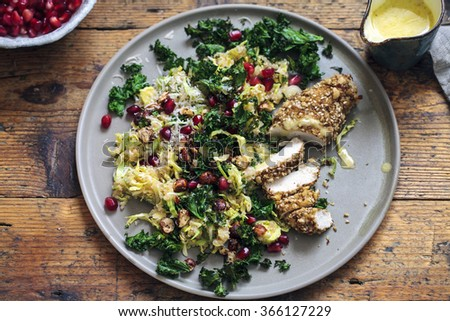 Quinoa, brussel sprouts, crispy kale and hazelnuts salad with dukkah crusted chicken - stock photo