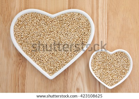 Quinoa grain super food in heart shaped porcelain dishes over beech wood background. - stock photo