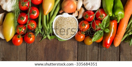Quinoa in a bowl and fresh vegetables on a wooden table - stock photo