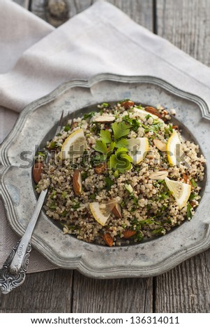 Quinoa salad with almonds and parsley served in old style plate - stock photo
