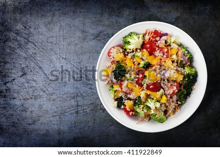 Quinoa salad with broccoli,bell peppers, carrot, onion and tomatoes on a rustic metal background. Superfoods concept. - stock photo