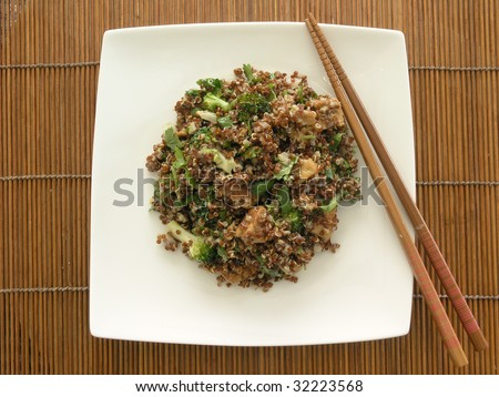 quinoa salad with broccoli, tofu, cilantro, and sesame ginger dressing on a white squared china plate placed on a bamboo matte - stock photo