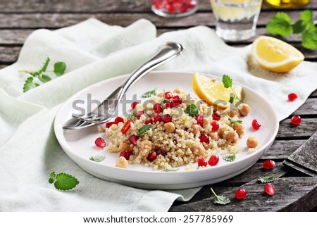 Quinoa salad with chickpeas,pomegranate and mint on a rustic wooden table.Selective focus. - stock photo