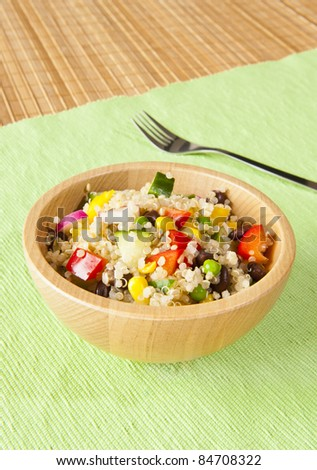 Quinoa salad with colorful vegetables in a wooden bowl - stock photo